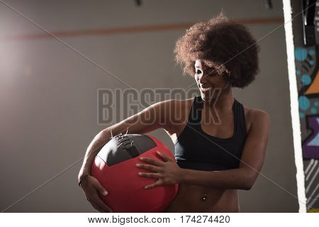 portrait of a young beautiful African American women carrying crossfit ball in gym