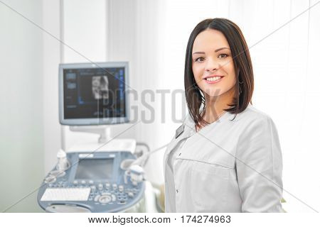 Smiling brunette female doctor standing against ultrasound equipment and computer. Professional in white uniform posing at camera in cabinet at modern hospital.