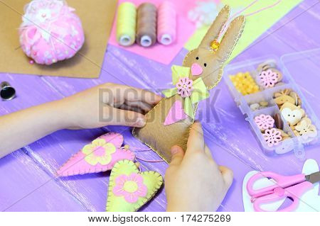 Child holds a felt Easter bunny in his hands. Child made a felt bunny with hearts for Easter. Tools and materials for kids creativity on a wooden table. Symbolic Easter decoration crafts for kids