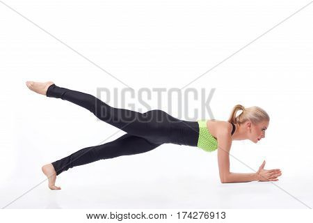 Enjoying health benefits of sports. Young female with perfect sporty toned body doing planking exercise raising her leg isolated gym workout plank fitness concept copyspace