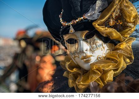 Golden Venetian Carnival Mask. Wonderful masked participant of the carnival celebrations in St. Mark's basin. Blurred background.
