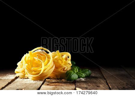 Tasty Fresh Colorful Ingredients for Cooking Pasta Tagliatelle with Fresh Basil and Tomatoes. Wooden Table Background.