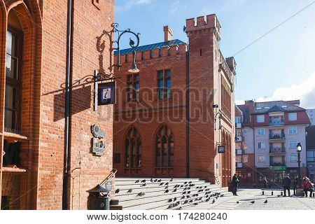 Kolobrzeg Poland - February 24 2017: People are resting near the building of Town Hall in an old town at sunny day