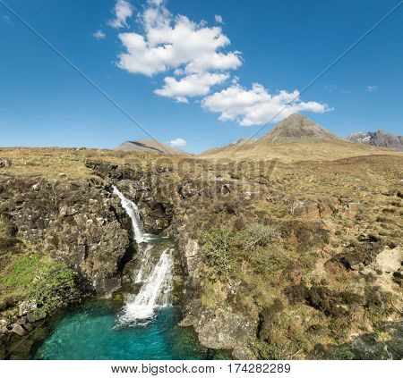 Beauty waterfall with amazing cyan colored water pool in springtime. Clear and sunny day in Glen Brittle valley Isle of Skye, Scotland. Cuillin Hills in Background.