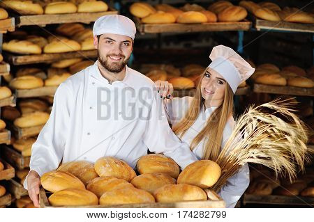 Girl with a guy in white overalls are holding fresh bread and bakery in the background of shelves with bakery