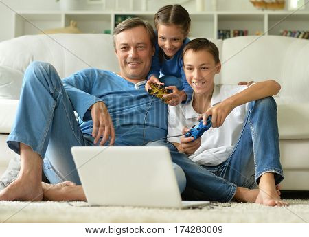 father with kids playing computer games at home
