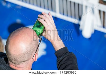 Anonymous an drinking beer out of a bottle