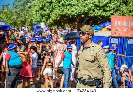 RIO DE JANEIRO, BRAZIL - FEBRUARY 28, 2017: Serious policeman of Municipal Guard in sunglasses working during Bloco Orquestra Voadora on the background of crowd of people, Carnaval 2017