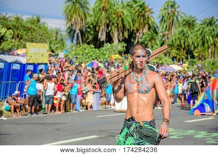 RIO DE JANEIRO, BRAZIL - FEBRUARY 28, 2017: One of the artist of Bloco Orquestra Voadora with naked torso carrying his stilts on his shoulder on the background of crowd of people, Carnaval 2017