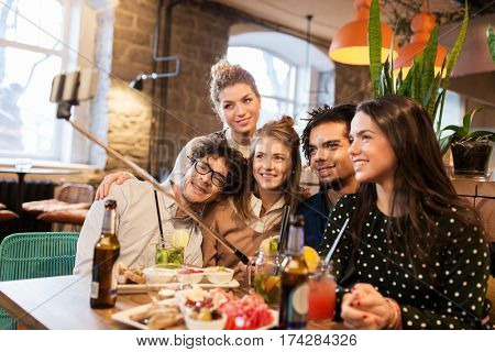 leisure, technology, friendship, people and holidays concept - happy friends with food and drinks taking picture by smartphone selfie stick at bar or cafe