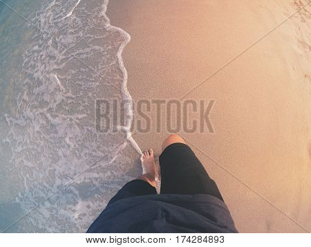 Point of view shot of a man walking along the water on a beach. Shot from above on a sunny summer day.