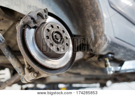 auto service and maintenance concept - car brake disc at repair station