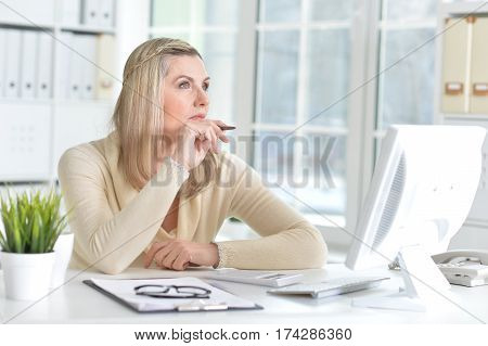 pensive mature woman using computer and making notes