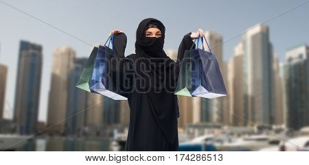 sale, consumerism and people concept - muslim woman in hijab with shopping bags over dubai city street background