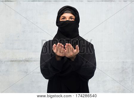 religion, faith, islam and people concept - praying muslim woman in hijab over gray concrete wall background