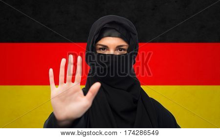 gesture, immigration, religious prohibition and people concept - muslim woman in hijab showing stop sign over german flag background
