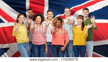 diversity, race, ethnicity and people concept - international group of happy smiling men and women waving hand over english flag background