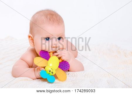Cute baby girl on white background. Baby in diaper with toy