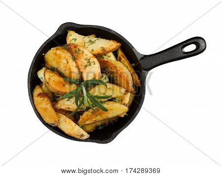 Fried potatoes with fresh rosemary in cast-iron pan isolated on white wooden background. Rustic style. Top view.