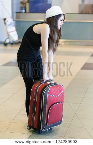 Young woman with heavy suitcase in the airport