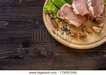 Slices of raw meat. Pork escalope on a wooden board. With the ingredients for cooking. Space for text