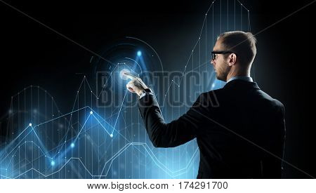 business, future technology, cyberspace and people - businessman in suit and glasses pointing finger to virtual diagram chart projection over black background