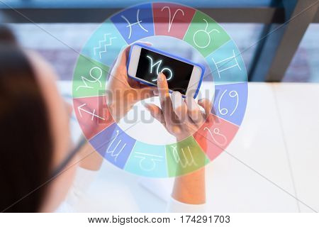 astrology, horoscope, people and technology concept - close up of young woman in eyeglasses with smartphone and capricorn zodiac sign  at office