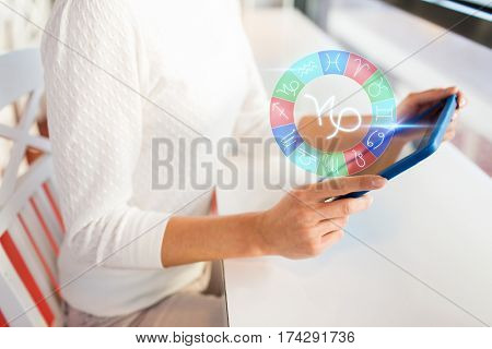 astrology, horoscope, people and technology concept - close up of woman with tablet pc computer and capricorn zodiac sign at cafe