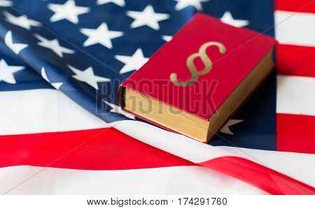 justice, law, civil rights and nationalism concept - close up of american flag and lawbook