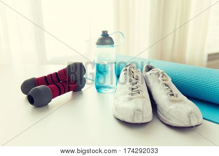 sport, fitness and objects concept - close up of bottle with water, dumbbells, sneakers and sports mat at home