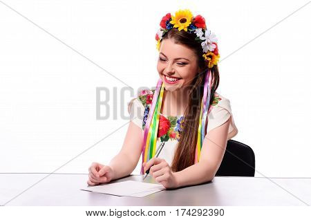 Happy Businesswoman With Note And Pen By A Desk.in The Ukrainian National Costume