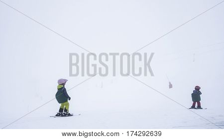 A children's ski school, in thick fog, in the the French Alps, showing two small children on the piste