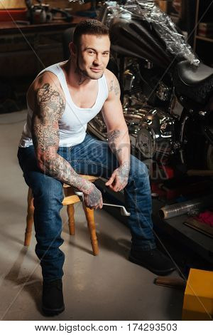 Happy to be here. Sporty smiling motorcyclist wearing white T-shirt holding his right hand with wrench on his knees looking straight at camera