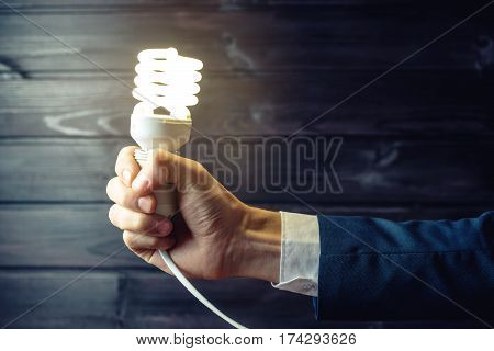 Hand Holds A Glowing Light Bulb. Creative Idea In Business