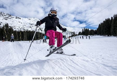 Young, female skier, wearing pink trousers, jumping in the air on skis, on a sunny day in Meribel, the French Alps, looking to camera as she is in the air.