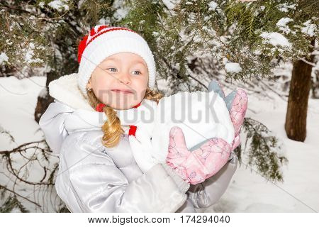 Close up portrait of adorable happy little girl grinning happily at the camera on a sunny winter's day