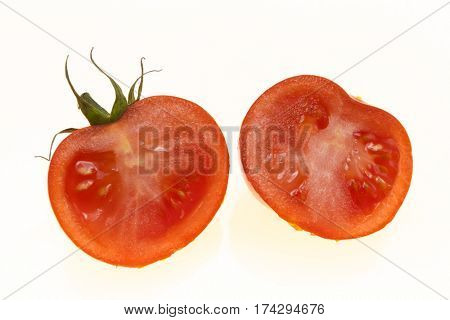 Ripe tomatoes cut into two halves on white background.