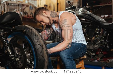 I am infatuated. Brutal young male person covered with tattoo wearing jeans and T-shirt sitting behind his motorcycle while looking at big wheel