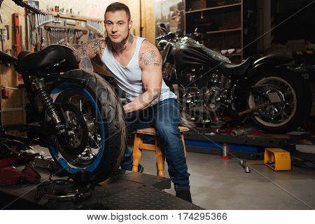 Enthusiasm for motorbike. Brutal male person covered with tattoo wearing jeans and T-shirt sitting behind his motorcycle while looking at camera