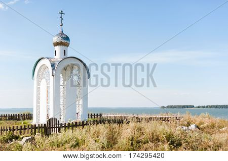 Orthodox Chapel White With A Transparent Façade On The Background Of The Panorama Of The Sea And Blu