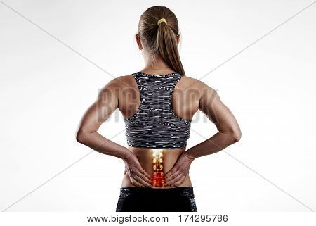Fitness woman holding painful back after training. Concept of spine injury and inflammation.
