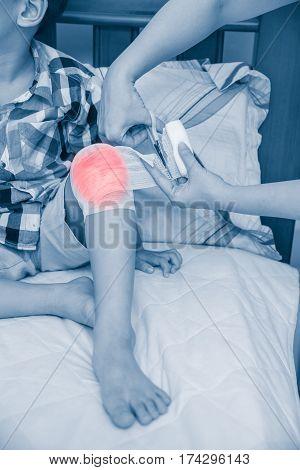 Child Injured. Mother Bandaging Son's Knee.