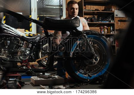 Like shade. Serious bearded man having relief body being keen on motorbikes posing behind his iron friend