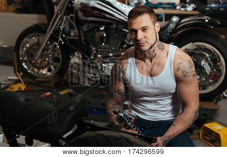 Right detail. Brutal young biker with tattoo wearing jeans and white T-shirt sitting on the background of big motorcycle while looking at camera