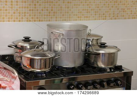 Steel Pots And Small Saucepan On The Stove Inside The Restaurant