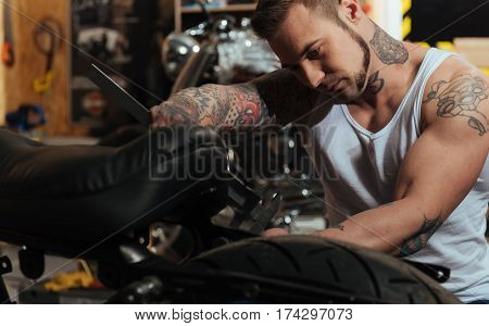 Like toolware. Serious young bearded master wearing white tee shirt spending time in workshop while repairing his motorbike