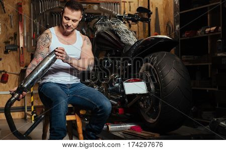 Think about pure air. Handsome bearded man having positive thoughts sitting on the chair next to the motorcycle while looking at gas vent