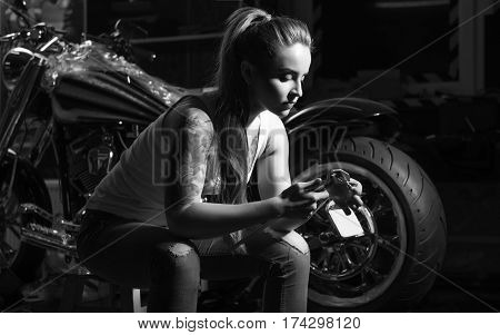 Girls love bikes. Black and white photo of young female person being keen on tattoo sitting on the chair while looking at detail
