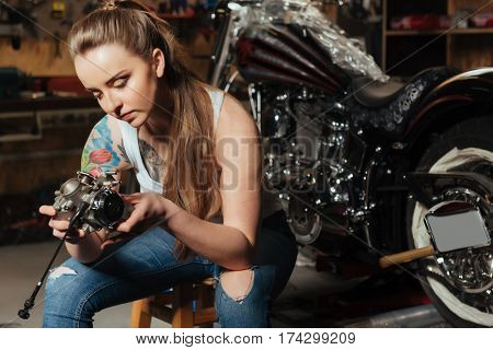 Brutal style. Professional female with tattoo sitting seriously looking at detail from motorbike stooped while leaning on knees