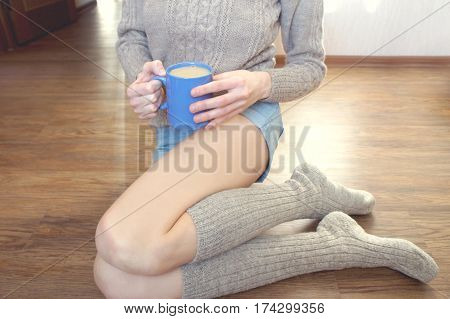 Girl with denim shorts, sweater and socks is sitting on a hardwood floor and holding a blue mug of coffee with milk